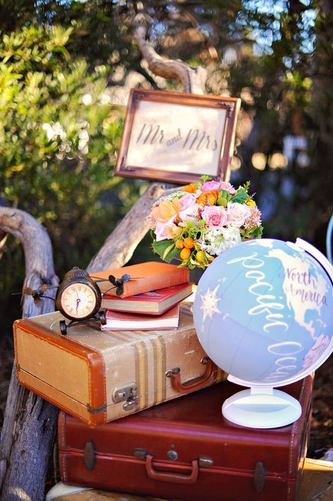 a stack of vintage suitcases, books, right blooms, a fun plane, a globe and a sign is cool decor for a vintage travel-themed wedding