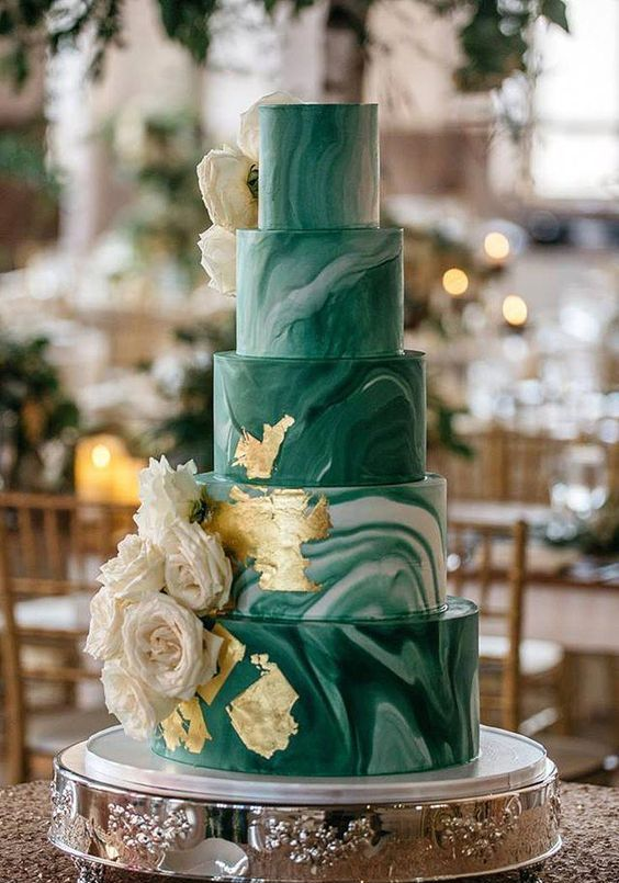 a statement five-tier green marble wedding cake with gold leaf and white roses is a fantastic idea for any glam wedding