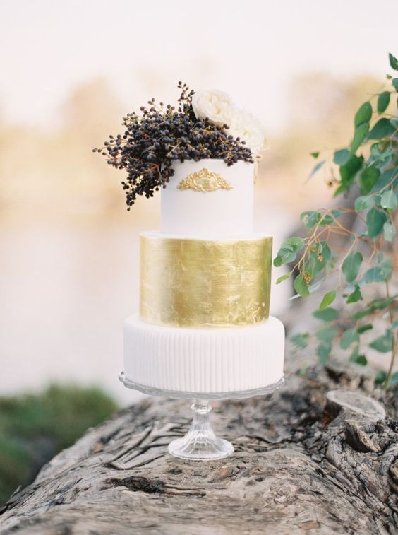 a stylish art deco wedding cake with white and a gold leaf tiers, privet berries, white bloms