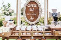 a stylish coffee bar with a large vintage sign, coffee cups, liquors and various sweets and blooms for decor