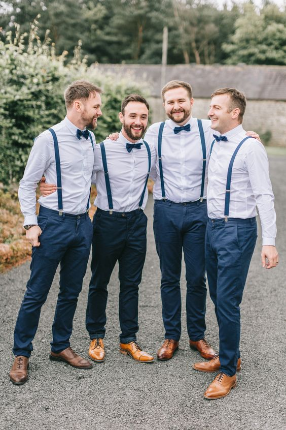 a stylish groom's outfit with navy pants and suspenders, light blue shirts, navy bow ties, brown shoes