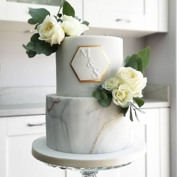 a stylish modern marble and white wedding cake with a hexagon with monograms and white blooms