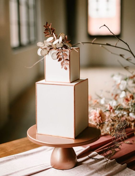 a stylish modern wedding cake with copper framing, copper herbs and foliage and white blooms