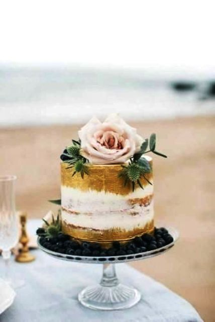 a stylish small naked wedding cake with gold leaf, thistles, eucalyptus and a large blush flower on top