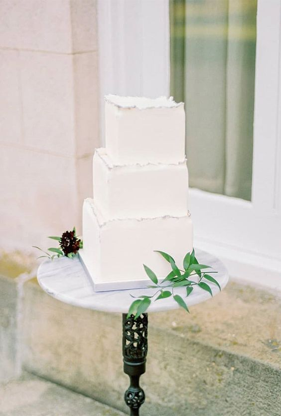a stylish square wedding cake in pure white with a raw silver edge is a beautiful option for a minimalist wedding