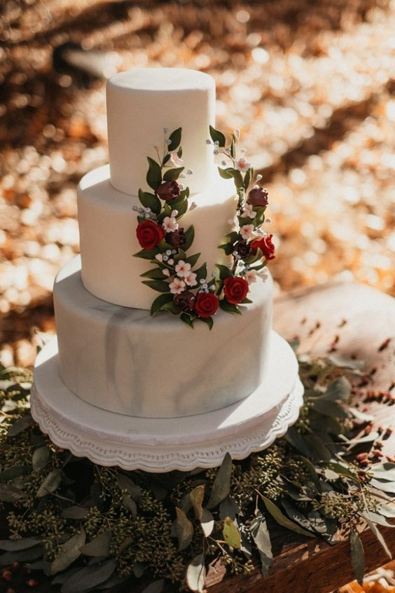 a stylish wedding cake with white and white marble tiers and a mini wreath of white and red blooms and greenery