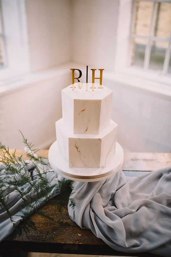 a stylish white hexagon wedding cake with gold touches and gold monograms is a lovely and cool idea to rock
