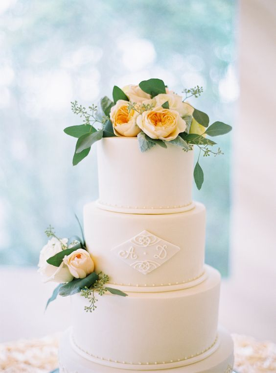 a stylish white wedding cake with a monogram on a rhomb, some peach blooms and greenery is very elegant