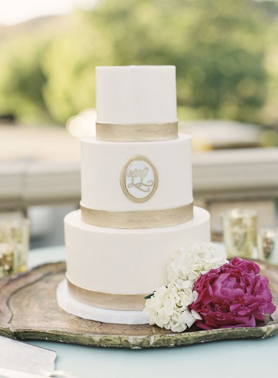 a stylish white wedding cake with gold ribbons and a monogram is a cool idea for many weddings, from a refined vintage one to a modern one