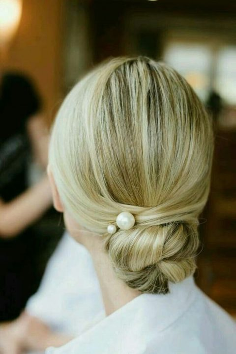 a super elegant twisted low bun with pearl pins and a sleek top for a minimalist bride