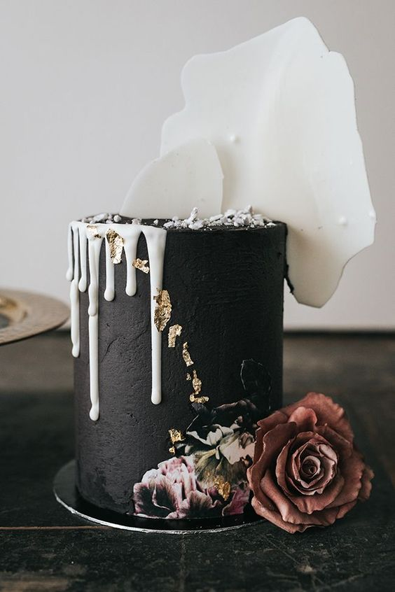 a textural black wedding cake with white dripping, gold leaf, painted and fresh blooms and white chocolate shards