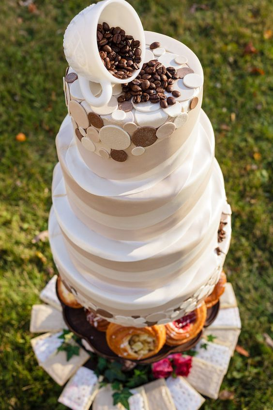 a textural buttercream wedding cake with coffee beans and a cup on top plus coffee-inspired detailing