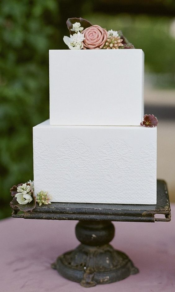 a textural white square wedding cake with fresh and sugar blooms and fresh berries on top