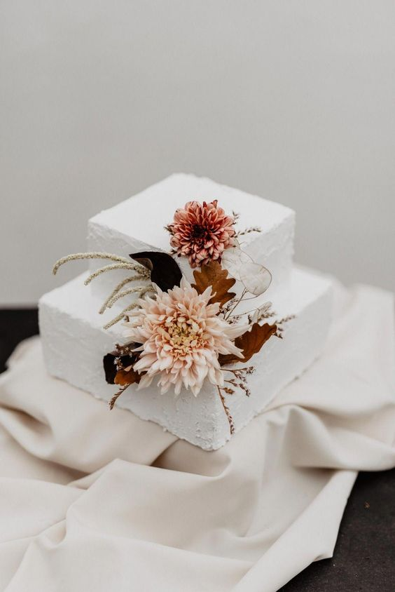 a textural white wedding cake with blush blooms, dried leaves and herbs for a fall wedding