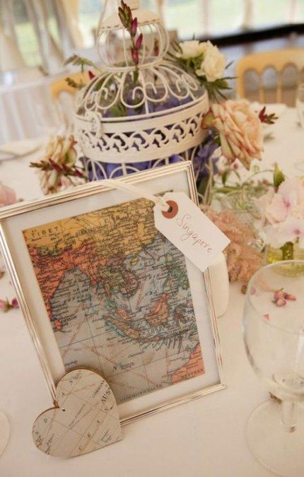 a travel-themed wedding centerpiece of a cage fileld with flowers and greenery, a map sign with a tag