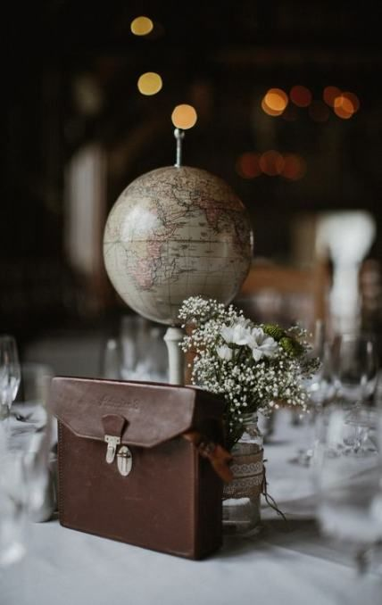 a travel wedding centerpiece of a globe, a suitcase, a neutral bloom and greenery arrangement