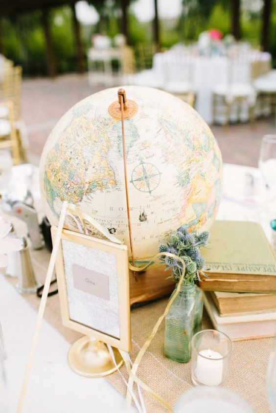 a travel wedding centerpiece of stacked books, a sign, thistles in a bottle and a large globe