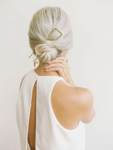 a twisted low bun with a volume on top and a statement hair pin for a minimalist bride