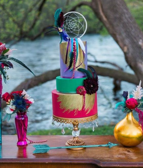 a vibrant boho wedding cake in fuchsia, turquoise and purple, with gold leaf and colorful blooms and a dream catcher