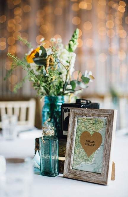 a vintage travel-themed wedding centerpiece of a vintage camera, neutral blooms and greeneyr, a map sign