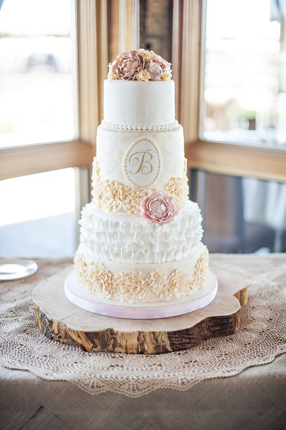 a vintage wedding cake with neutral tiers, a ruffle, a floral and a plain one, with sugar blooms, a monogram and some blooms on top