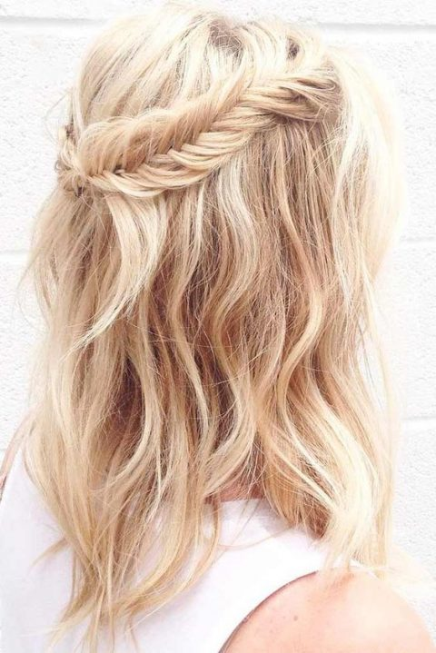 a wavy and textural half updo with a fishtail braid to frame it is a relaxed and cute option