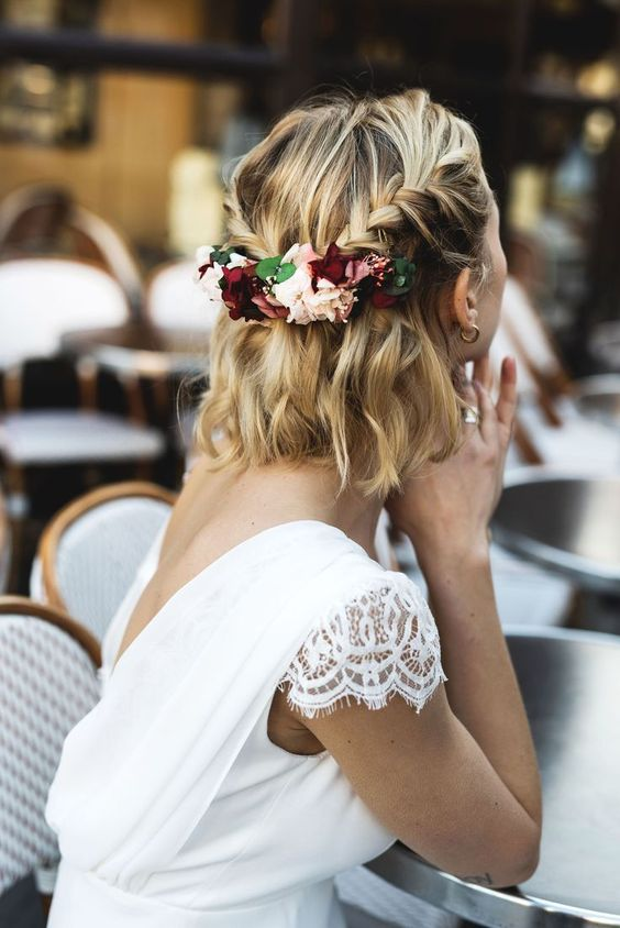 a wavy half updo with two braids secured with fresh flowers and greenery is a chic idea