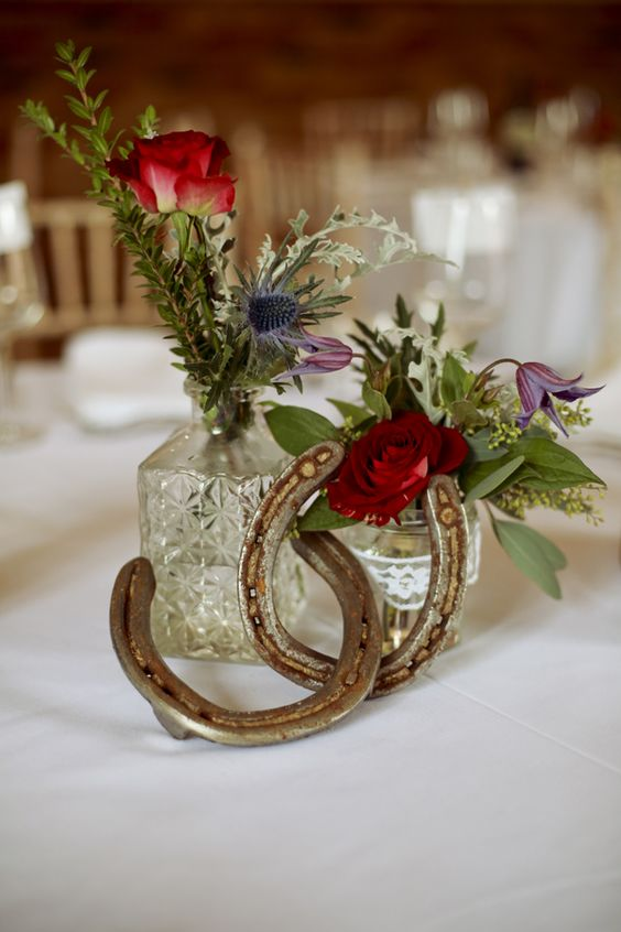 a wedding centerpiece made of vintage glasses, bold blooms and greenery and horseshoes for a rustic wedding