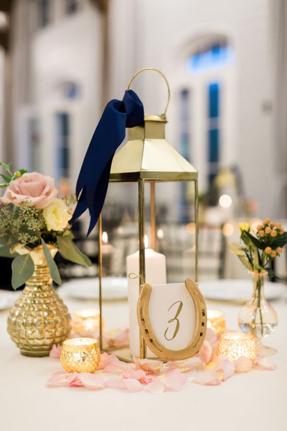 a wedding centerpiece of a candle lanter, pink blooms in vases, candles, pink petals and a horseshoe with a table number