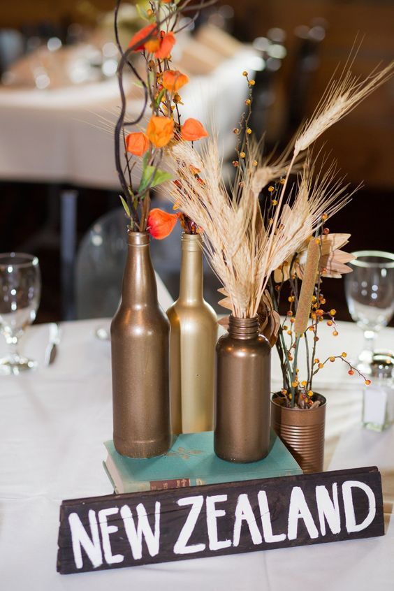 a wedding centerpiece with a name, dried blooms and greenery in bottles and jars for a travel-themed wedding