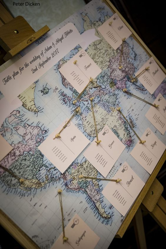 a wedding seating chart styled as a world map with some cards is a creative idea for a travel-themed wedding
