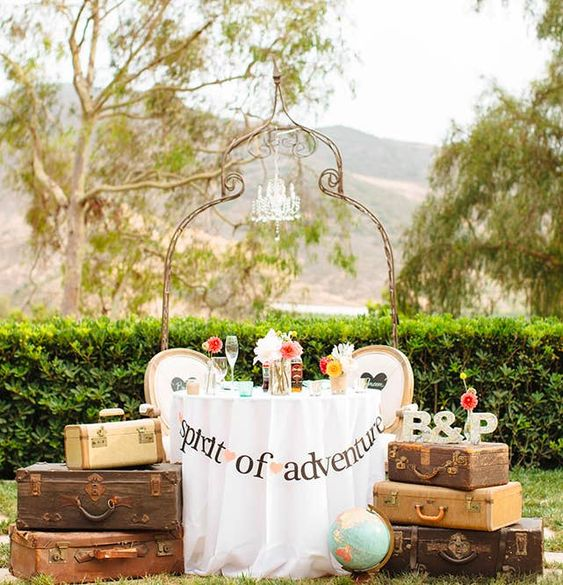 a wedding sweetheart table with suitcases on both sides, monograms, blooms and a globe by the table