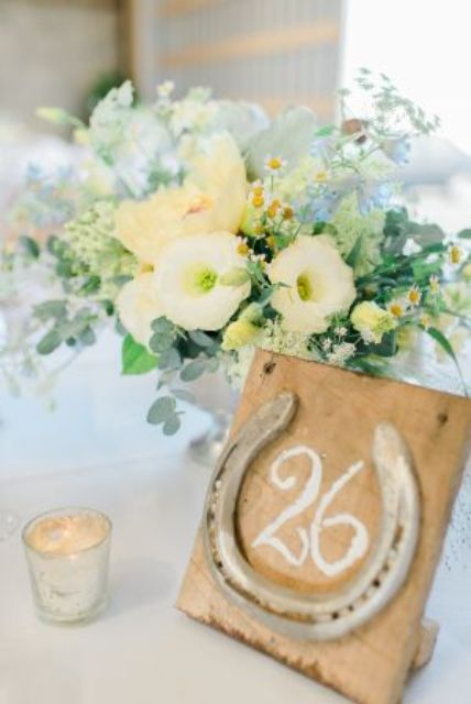 a wedding table number made of a plywood piece and a horseshoe is a cool idea in rustic style