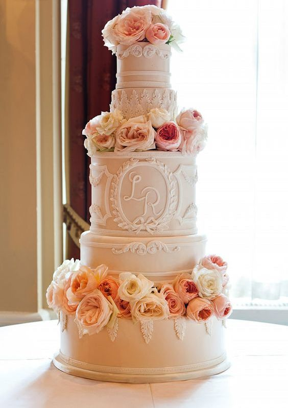 a whimsical tan wedding cake with many tiers, white sugar patterns and monograms, with pachy and orange blooms that decorate it