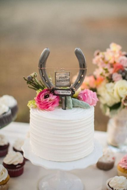 a white buttercream wedding cake topped with pink blooms, greeneyr and a horseshoe with a sign