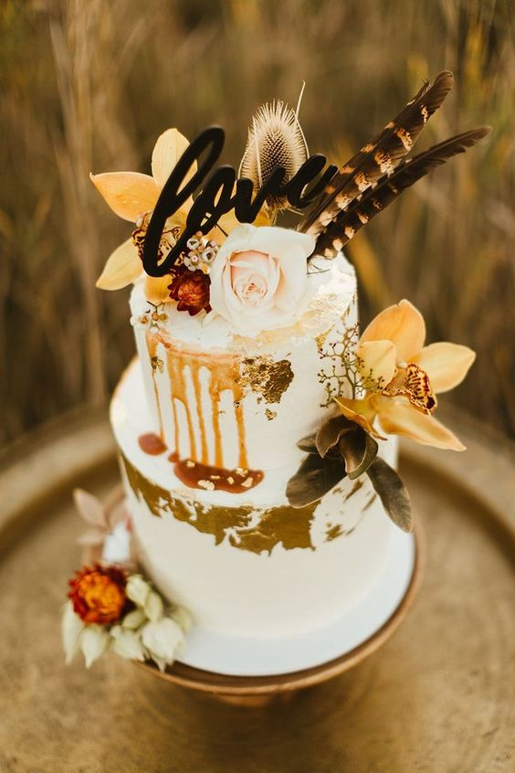a white fall boho wedding cake with gold leaf, moody blooms and foliage, blush rose and feathers on top