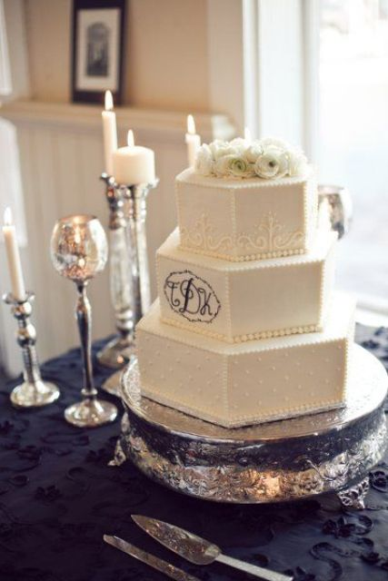 a white hexagon wedding cake with patterns and polka dots, with black monograms and white blooms on top