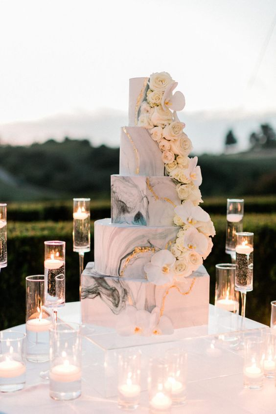 a white marble hexagon wedding cake with gold leaf touches and white roses and rochids surrounded with candles