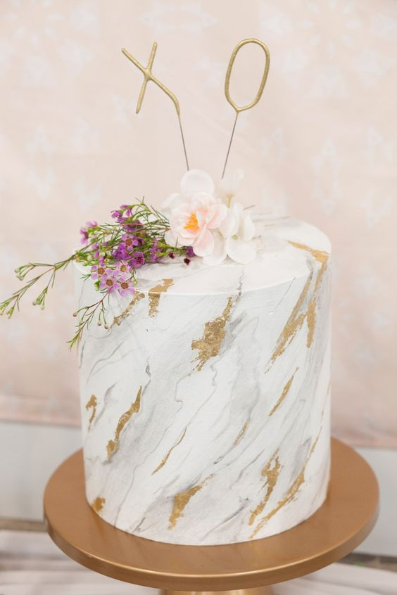 a white marble wedding cake with godl touches, blush and bold blooms plus XO toppers