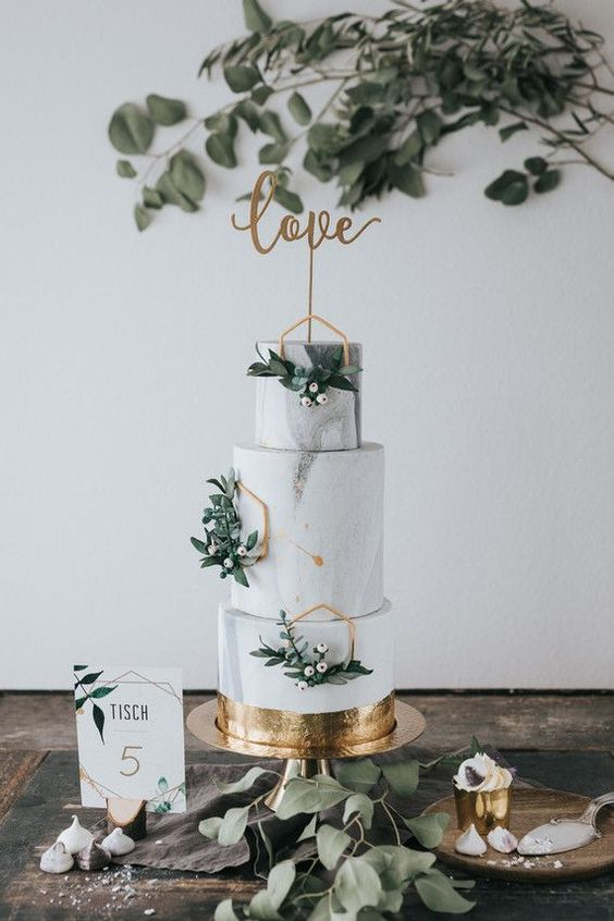 a white marble wedding cake with gold hexagons, greenery and berries plus a gold calligraphy topper