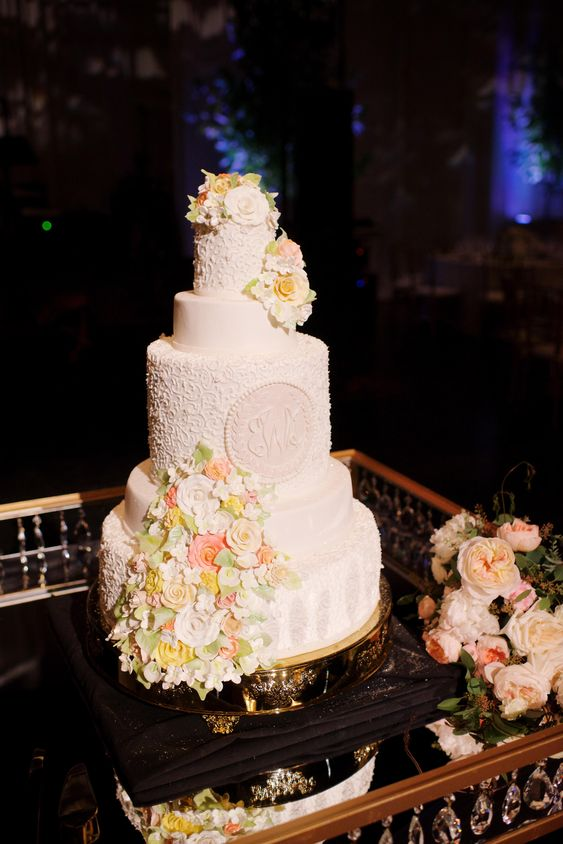 a white patterned wedding cake with monograms and bright sugar blooms and greenery is a chic idea