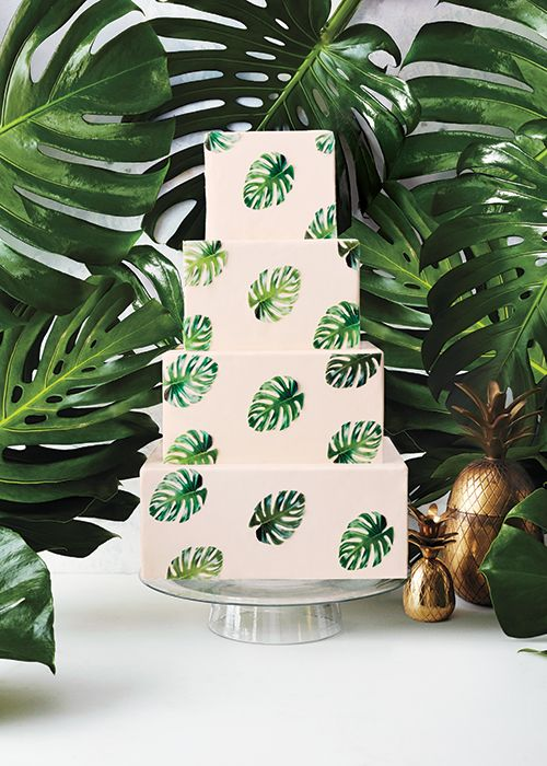 a white square wedding cake decorated with tropical leaves for a modern tropical wedding