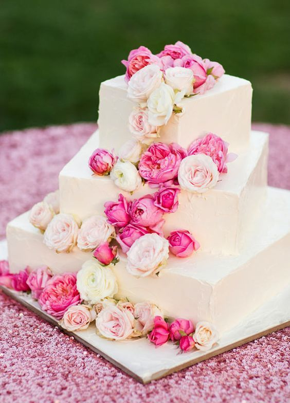a white square wedding cake with pink and blush cascading blooms is a beautiful option for summer