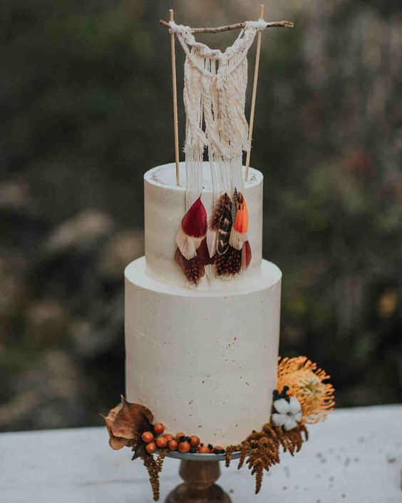 a white textural wedding cake with bright feathers and a macrame topper plus bold blooms for a fall boho wedding