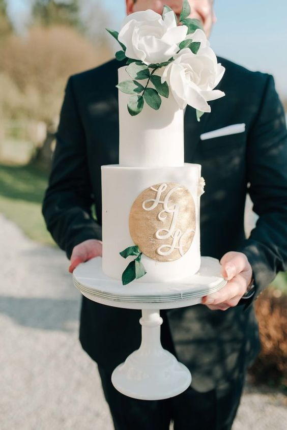 a white wedding cake with a gold circle and monograms, white blooms and greenery is a timeless idea for a chic wedding
