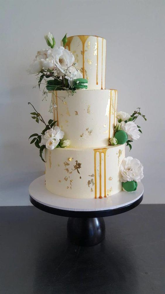a white wedding cake with gold leaf, caramel drip, white blooms, greenery and green macarons