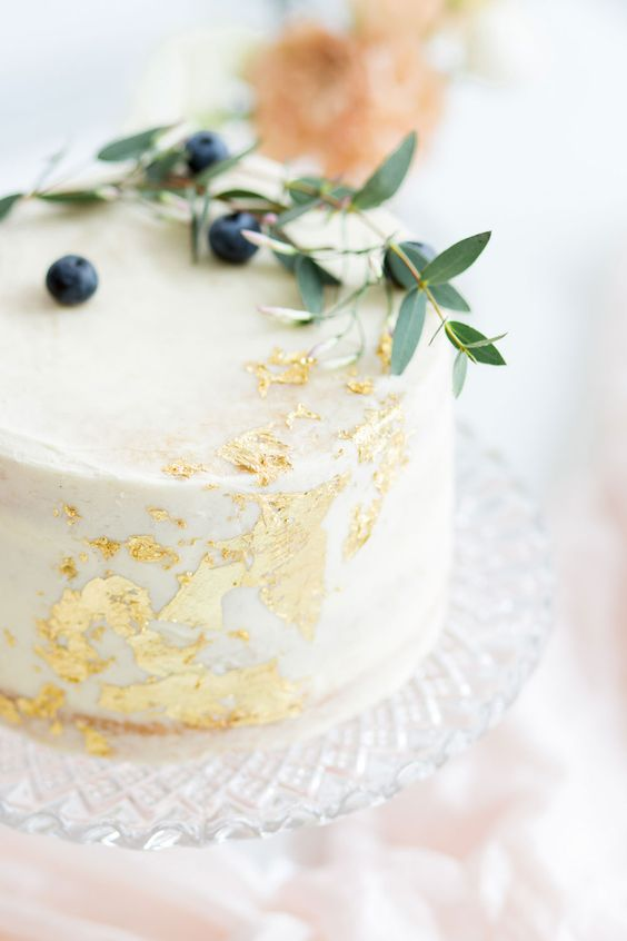 a white wedding cake with gold leaf, greenery and berries on top is a stunning idea for a casual wedding