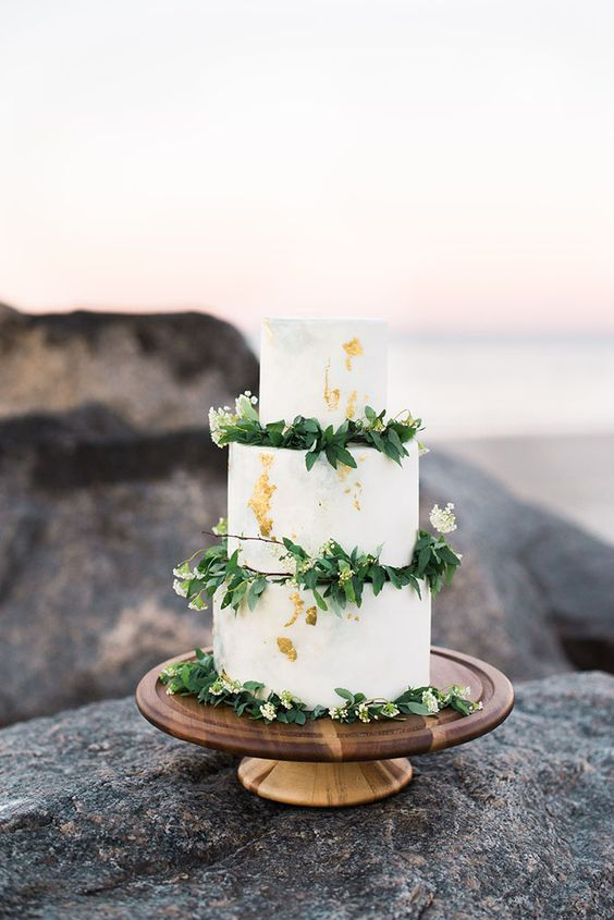 a white wedding cake with gold leaf, greenery and white blooms is a universal cake for any season