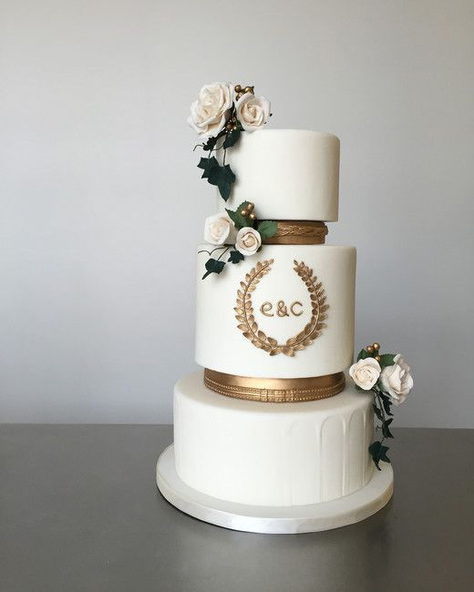 a white wedding cake with gold mini tiers, with sugar blooms and leaves plus a gold leaf wreath and monograms for an exquisite modern wedding
