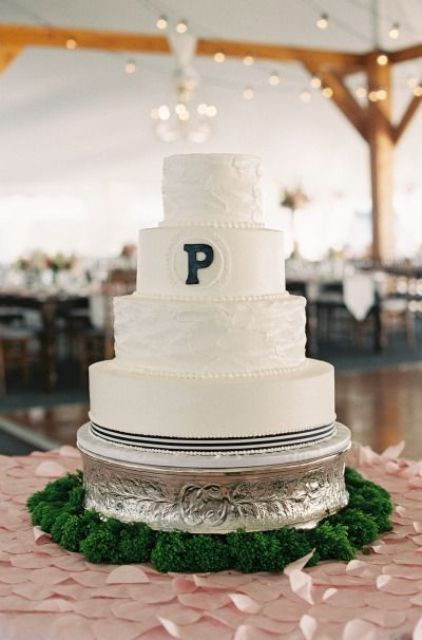 a white wedding cake with plain and textural tiers and a single black monogram is a stylish and easy to try idea